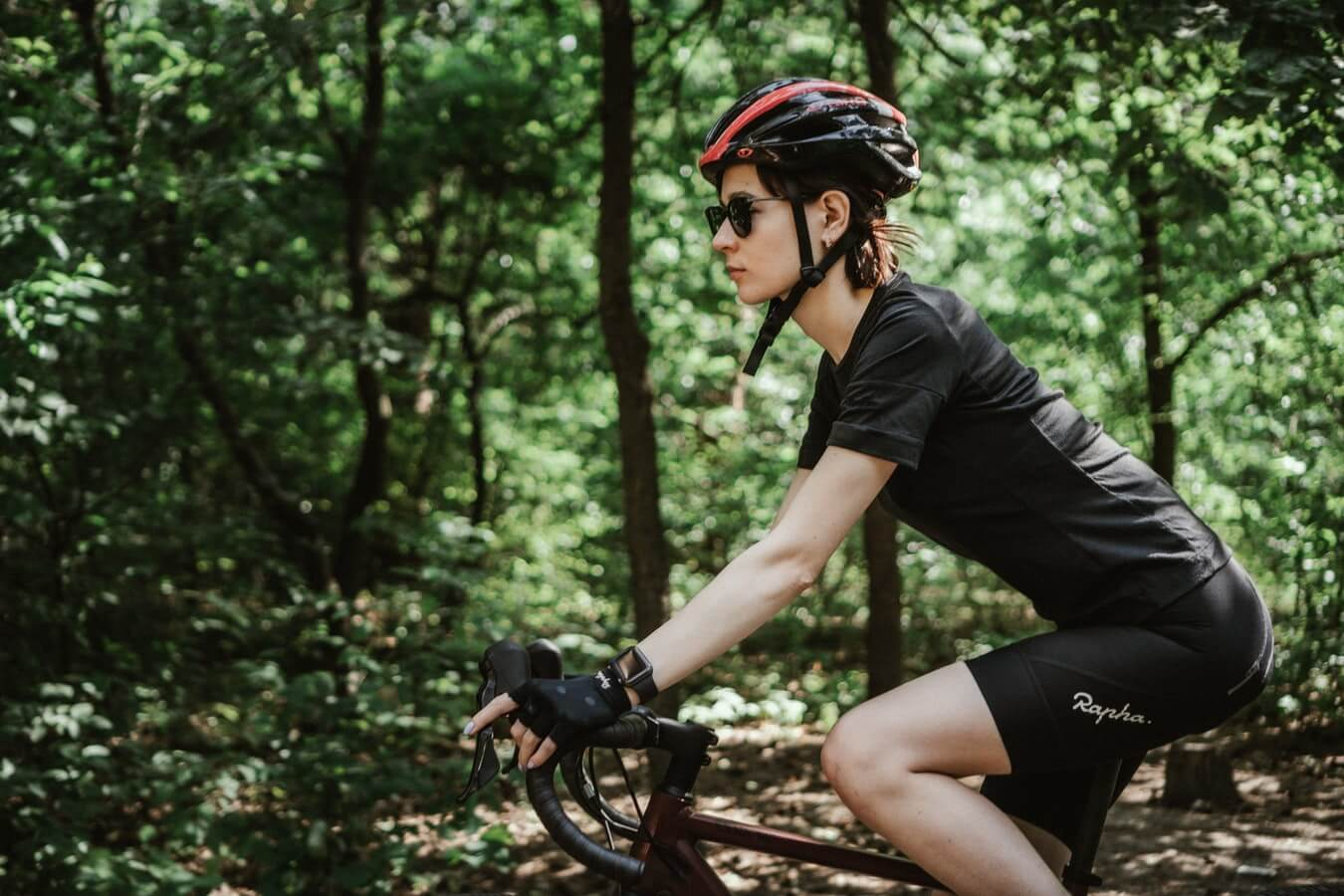 A girl is riding her bike with a cycling gloves on the forest
